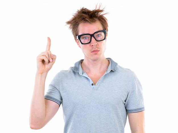 Porträt des jungen gutaussehenden skandinavischen nerd-mannes, der brillen trägt, die gegen weiße wand lokalisiert werden