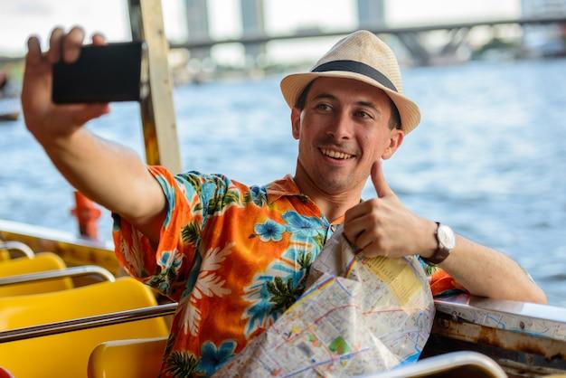 Porträt des jungen gutaussehenden touristenmann-reitboots als öffentliche verkehrsmittel in der stadt bangkok