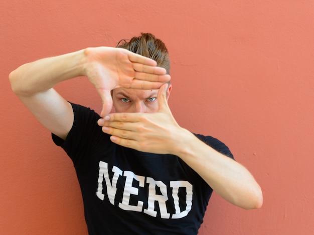 Porträt des jungen gutaussehenden touristenmannes als nerd gegen farbigen hintergrund draußen