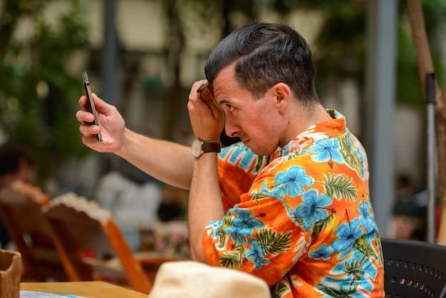 Porträt des jungen gutaussehenden touristenmannes am restaurant in der stadt im freien