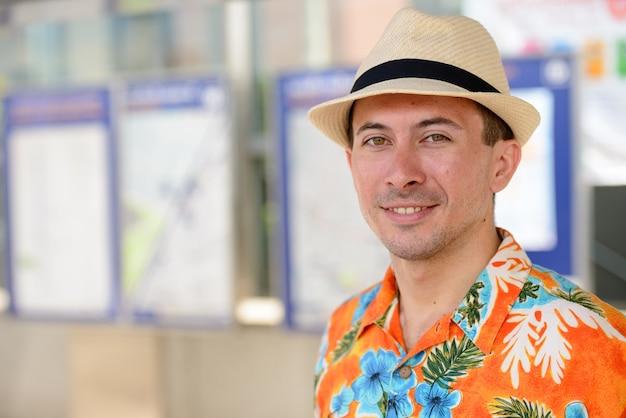 Porträt des jungen gutaussehenden touristenmannes am u-bahn-bahnhof in der stadt