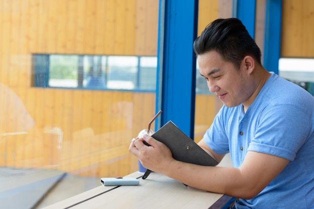 Porträt des jungen gutaussehenden übergewichtigen philippinischen mannes, der am kaffeehaus entspannt