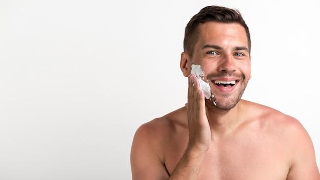 Porträt des jungen hemdlosen mannes, der den rasierschaum steht gegen weiße wand anwendet
