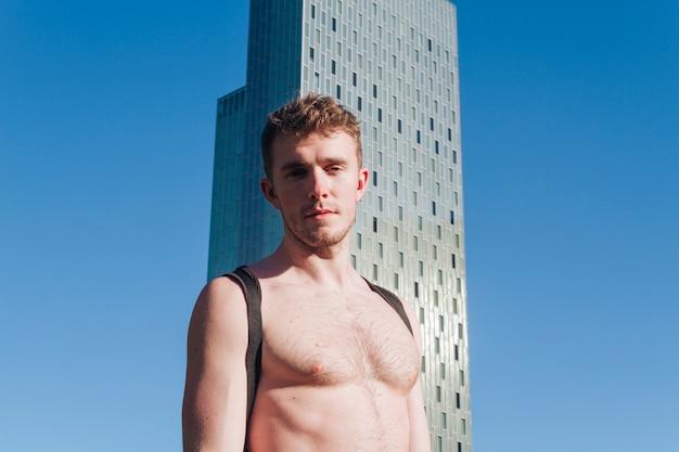 Porträt des jungen hemdlosen mannes, der kamera betrachtet