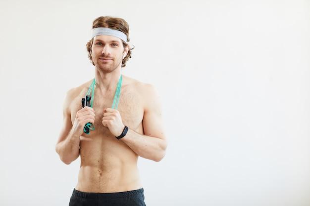 Porträt des jungen hemdlosen mannes mit springseil, der kamera lokalisiert auf weißem hintergrund betrachtet