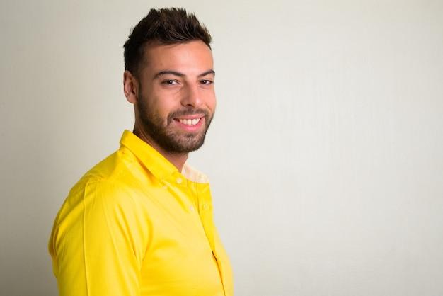 Porträt des jungen hübschen bärtigen geschäftsmannes, der gelbes hemd auf weiß trägt