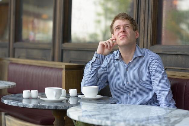 Porträt des jungen hübschen blonden geschäftsmannes, der am kaffeehaus draußen entspannt