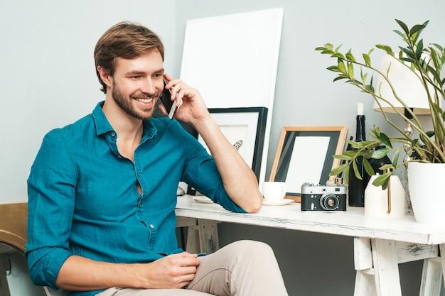 Porträt des jungen hübschen geschäftsmannes. durchdachter mann gekleidet in blue jeanshemd. bärtiges model posiert im büro in der nähe des schreibtisches und spricht am telefon.