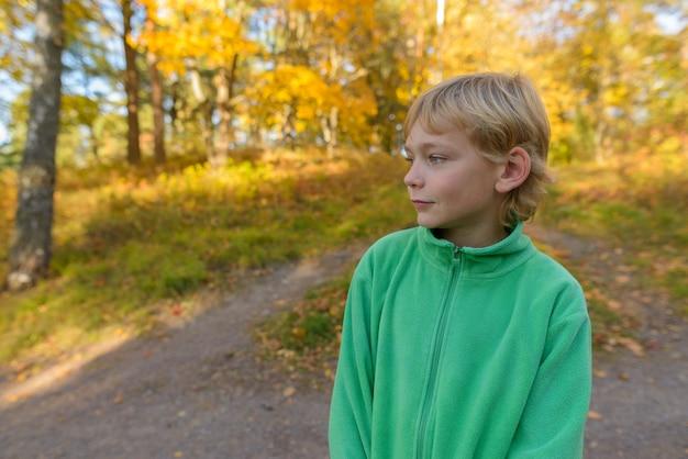 Porträt des jungen hübschen jungen mit den blonden haaren am park in der herbstsaison