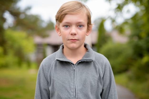 Porträt des jungen hübschen jungen mit den blonden haaren zu hause im freien