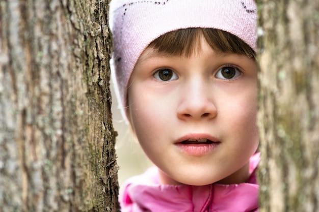 Porträt des jungen hübschen kindermädchens, das rosa jacke und kappe trägt, die zwischen bäumen im park stehen und warmen warmen tag im frühen frühling draußen genießen.