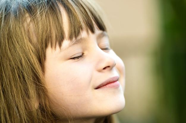 Porträt des jungen hübschen kindermädchens mit dem langen haar, das warmen warmen tag im sommer draußen genießt. nettes weibliches kind, das auf frischer luft draußen entspannt.