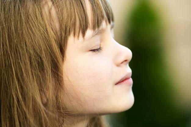 Porträt des jungen hübschen kindermädchens mit den langen haaren, die warmen sonnigen tag im sommer draußen genießen. nettes weibliches kind, das auf frischer luft draußen entspannt.
