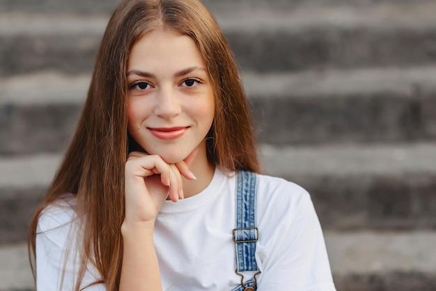Porträt des jungen hübschen mädchens, das auf treppen sitzt
