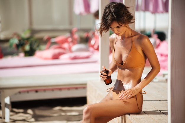 Porträt des jungen hübschen mädchens im bikini, das auf holzboden am strand sitzt und körperöl verwendet. schöne dame im beige badeanzug, der sonnenöl für sonnenbräune auf ihren körper schmiert