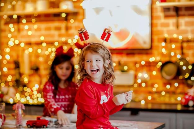 Porträt des jungen hübschen mädchens im roten weihnachtspyjama und im stirnband, die kleine weiße ratte in der küche gegen weihnachtshintergrund halten.