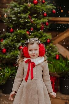Porträt des jungen hübschen mädchens im wintermantel und in den roten ohrenschützern, die auf der hölzernen terrasse aufwerfen