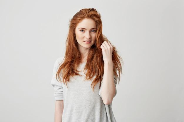 Porträt des jungen hübschen rothaarigen mädchens mit den sommersprossen, die rührendes haar lächeln.