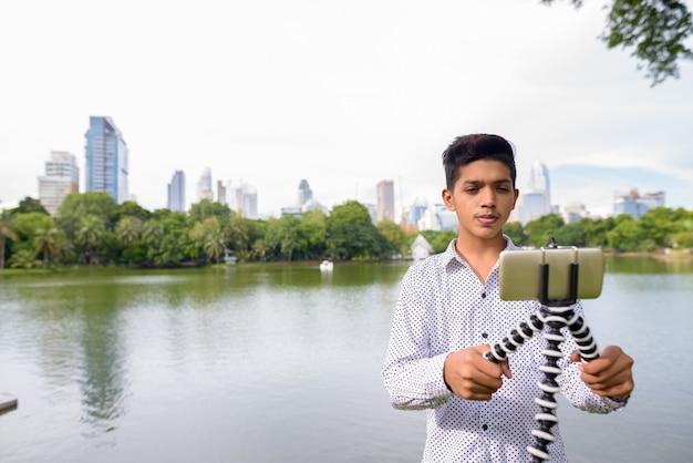 Porträt des jungen indischen teenagers, der am park entspannt