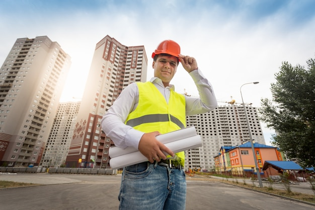 Porträt des jungen ingenieurs, der an neuen gebäuden mit blaupausen steht