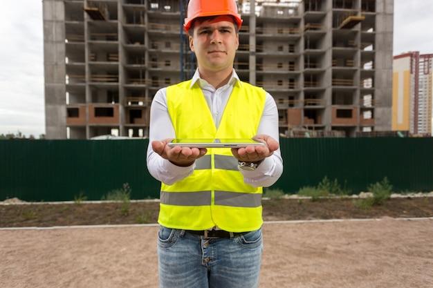Porträt des jungen ingenieurs, der gegen baustelle steht und digitale tablette hält. perfekt, um ihr bild auf dem tablet zu platzieren