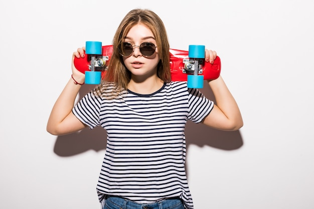Porträt des jungen jugendlich mädchens in der sonnenbrille, die mit skateboard beim stehen über weißer wand aufwirft