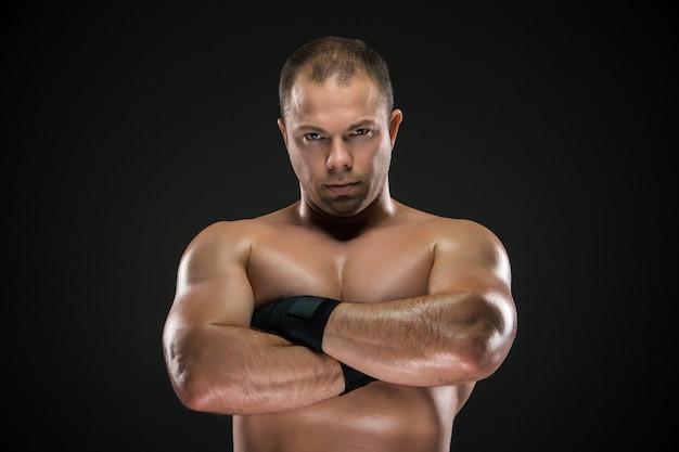 Porträt des jungen kaukasischen boxers mit gefalteten händen, die aufwerfen