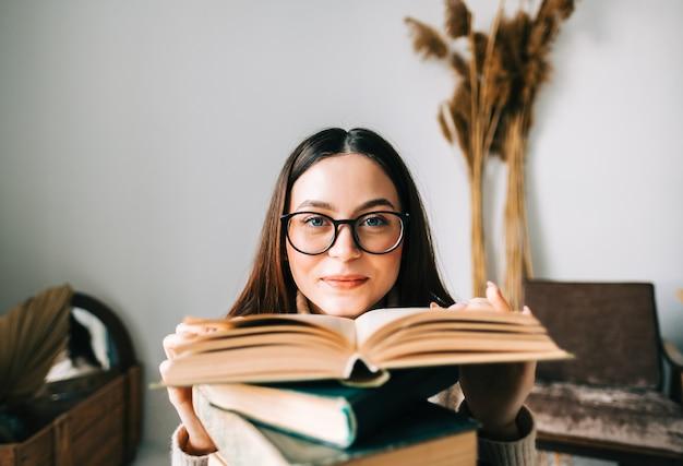 Porträt des jungen kaukasischen frauenstudenten in den brillen mit stapel büchern, kamera betrachtend.