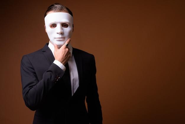 Porträt des jungen kaukasischen geschäftsmannes, der weiße maske trägt