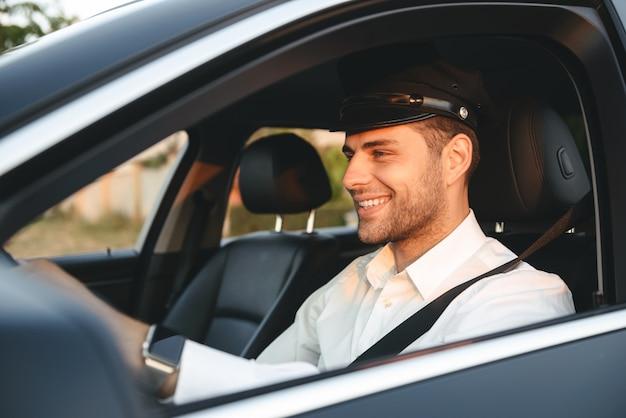 Porträt des jungen kaukasischen männlichen taxifahrers, der uniform und mütze trägt und auto anschnallt, das sicherheitsgurt befestigt