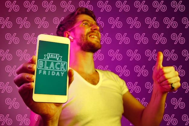 Porträt des jungen kaukasischen mannes, der handybildschirm auf purpurrotem hintergrund mit prozenten zeigt. verkaufskonzept, schwarzer freitag, cyber-montag, finanzen, geschäft. online-shops und zahlungsrechnung.