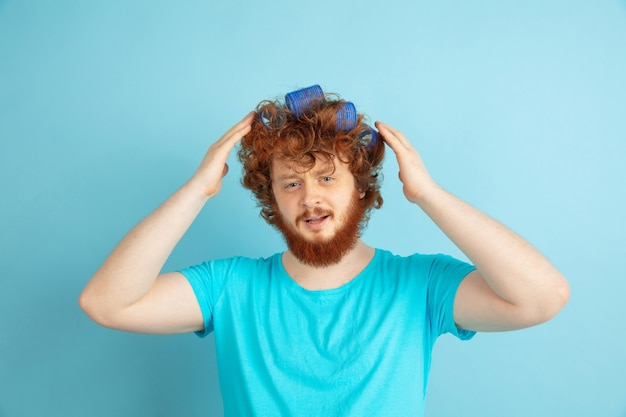 Porträt des jungen kaukasischen mannes in seiner schönheitstag- und hautpflege-routine. männliches model mit natürlichem rotem haar, das seine frisur macht, braucht mehr locken. körper- und gesichtspflege, natürliches, männliches schönheitskonzept.