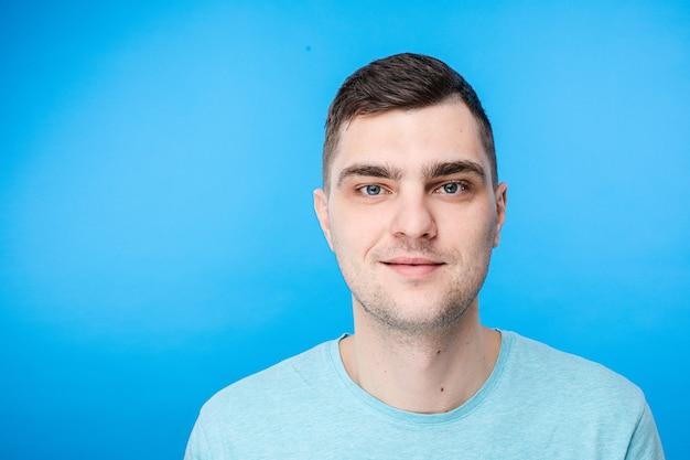 Porträt des jungen kaukasischen mannes mit kurzen dunklen haaren und hübschem gesicht ist glücklich