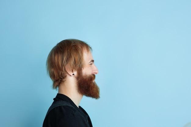 Porträt des jungen kaukasischen mannes sieht verträumt, niedlich und glücklich aus. aufschauen und auf blauem studiohintergrund denken. copyspace für ihre werbung. zukunftskonzept, ziel, träume, visualisierung.
