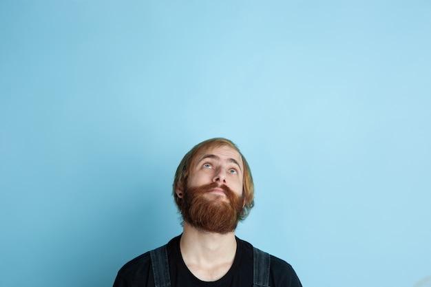 Porträt des jungen kaukasischen mannes sieht verträumt, niedlich und glücklich aus. nach oben schauen und über den blauen raum nachdenken