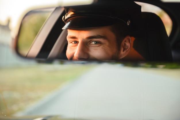 Porträt des jungen kaukasischen taxifahrers, der uniform und kappe trägt, auto fährt und im rückspiegel schaut