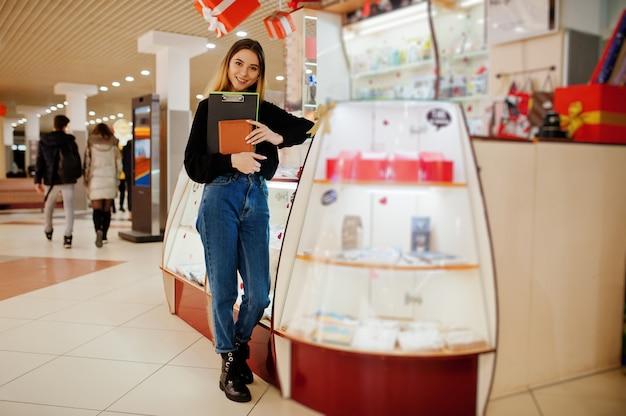 Porträt des jungen kaukasischen weiblichen verkäuferinnenstandes mit zwischenablage und notizbuch. kleines geschäft von süßigkeiten souvenirs shop.
