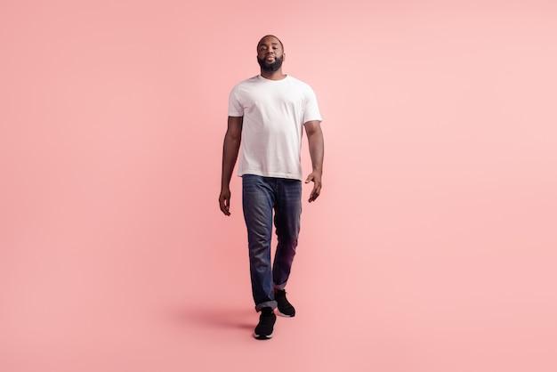Porträt des jungen kerls gehen blickkamera auf rosa hintergrund