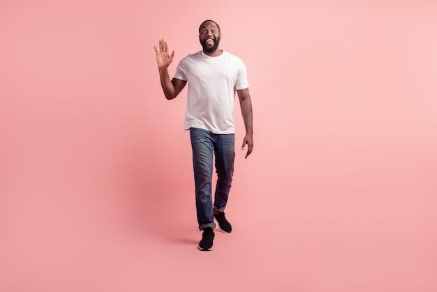 Porträt des jungen kerls gehen wellenhand auf rosa hintergrund
