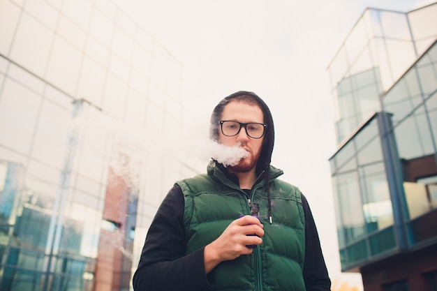 Porträt des jungen kerls mit großem bart in den gläsern, die eine elektronische zigarette gegenüber dem städtischen hintergrund verdampfen.