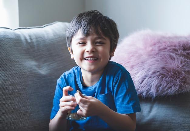 Porträt des jungen kindes, das geldmünzen im klaren glas hält, kind, das seine geretteten münzen zählt, glückliche kindheit, die auf sofahand sitzt, die münze hält