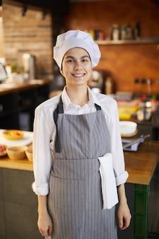 Porträt des jungen kochs, der chefhut trägt