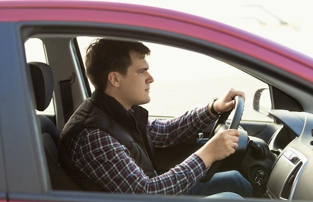 Porträt des jungen konzentrierten mannes, der ein auto fährt