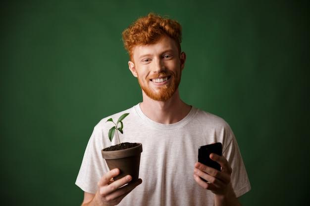 Porträt des jungen lächelnden bärtigen bärtigen jungen mannes, der gefleckte pflanze und handy hält