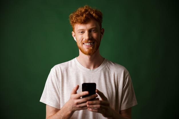 Porträt des jungen lächelnden bärtigen rothaarigen jungen mannes, der musik mit airpods hört