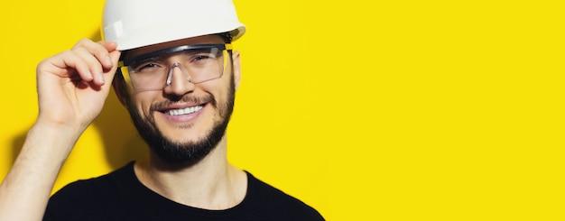 Porträt des jungen lächelnden bauingenieurs, der schutzhelm und schutzbrille auf gelb trägt