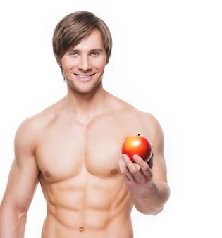 Porträt des jungen lächelnden bodybuilders, der apfel in seiner hand hält