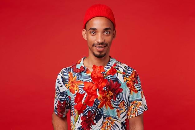 Porträt des jungen lächelnden dunkelhäutigen kerls, trägt im hawaiihemd und im roten hut, schaut in die kamera, mit einer roten blume, steht über rotem hintergrund.