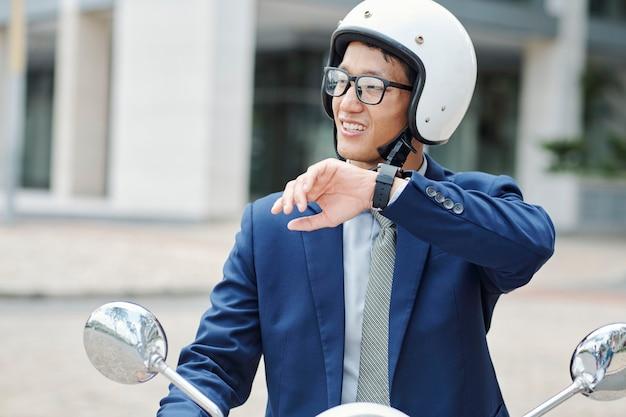 Porträt des jungen lächelnden geschäftsmannes im helm, der auf roller reitet und sprachnachricht über anwendung auf smartwatch aufzeichnet