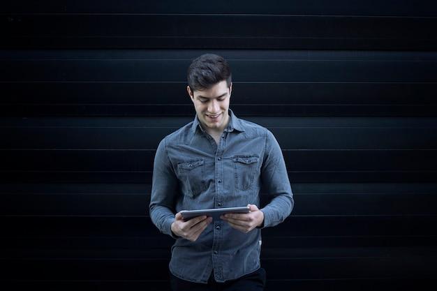 Porträt des jungen lächelnden gutaussehenden mannes, der tablet-computer hält und anzeige betrachtet